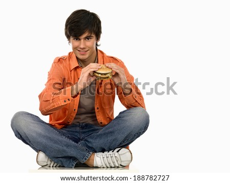 Young man eating. - stock photo
