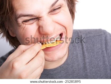 young man eating nachos with a funny grin close up - stock photo