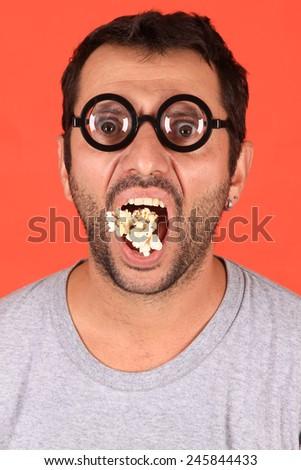 young man eating popcorn  - stock photo