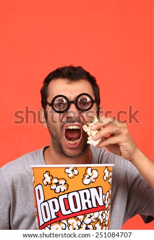 young man eating popcorn  - stock photo