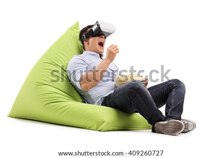 Young man eating popcorn and watching something on a VR goggles seated on a beanbag isolated on white background - stock photo