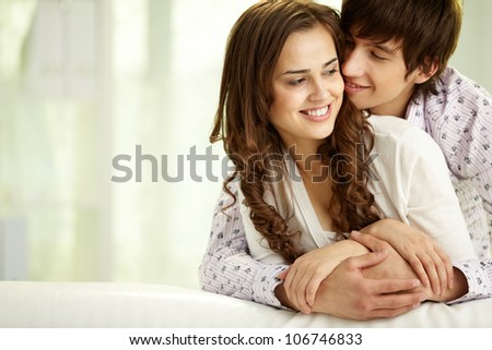 Young man embracing his happy girlfriend or wife - stock photo