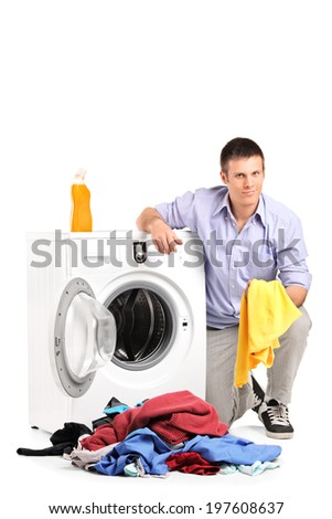 Young man emptying a washing machine isolated on white background - stock photo