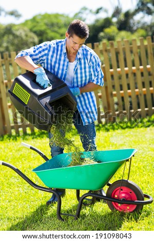 young man emptying lawnmower grass into a wheelbarrow after mowing - stock photo