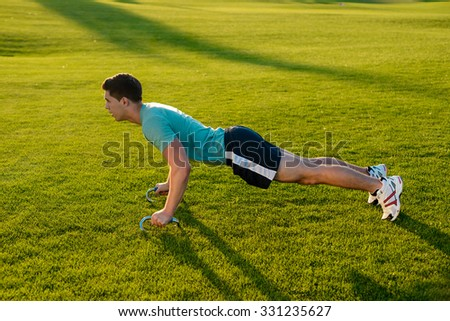 Young man engaged in sports in the street.  Guy shakes his muscles on the nature. Sports lifestyle. - stock photo