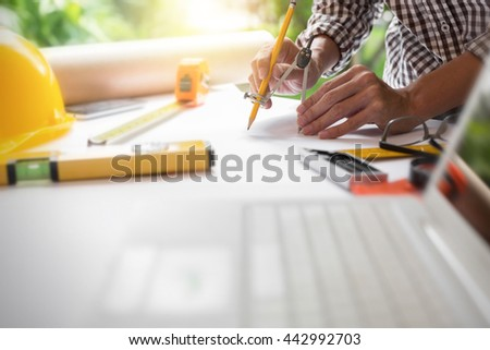 Young man engineer architect drawing a modern house blueprint project in the office at construction workplace, hipster view of photography. - stock photo