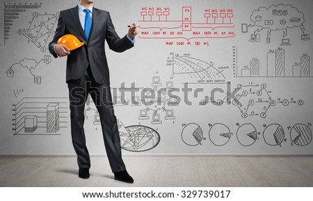 Young man engineer drawing marketing plan on screen - stock photo