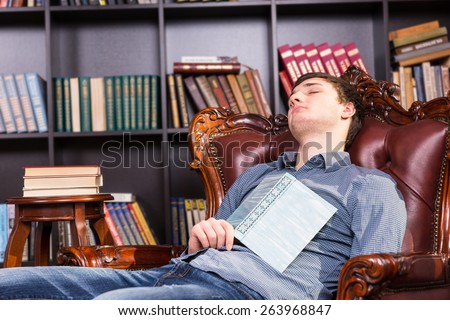 Young man enjoying a nap in the library relaxing in a comfy leather armchair with a hardcover book resting on his chest - stock photo