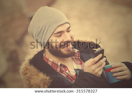 Young man enjoying coffee break while using his smartphone outdoors. - stock photo