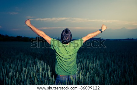 Young man enjoying his freedom/rejoicing from his success in the countryside, in a wheat field at dusk (color toned image) - stock photo