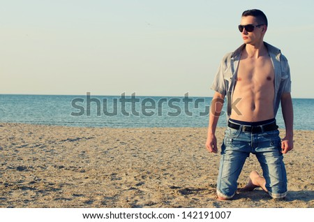 Young man enjoying his time on the beach - stock photo