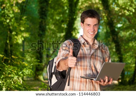 Young man enjoying in nature with bag pack and laptop - stock photo