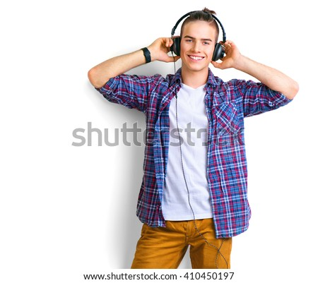 Young man enjoying music on his headphotes, listening to music. Handsome young stylish man in headphones standing against white background and smiling - stock photo