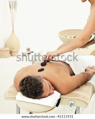 Young man enjoying the treatment in spa salon - stock photo