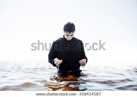 Young man experiencing the pain and disappointment, water through fingers - stock photo