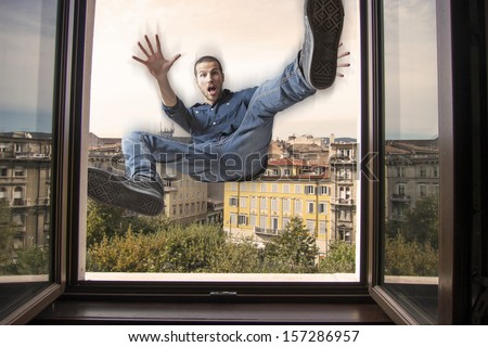 young man falling down a window - stock photo