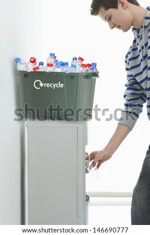 Young man filling glass of water from cooler with recycle bin on it - stock photo