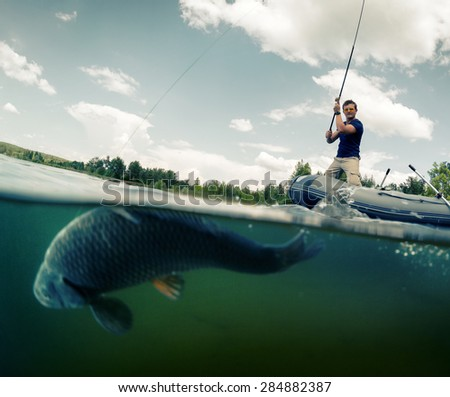 Young man fishing from the boat in the pond. Underwater split shot with fish on the foreground (fish is out of focus) - stock photo