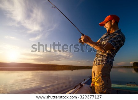 Young man fishing on the pond from the boat - stock photo