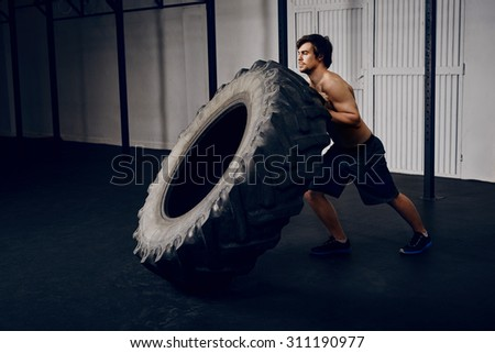 Young man flipping tire at gym - stock photo