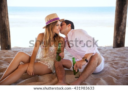 Young man flirting and whispering something in her girlfriend's ear while having a date and drinking beer at the beach - stock photo