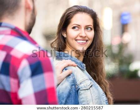 Young man flirting with a girl outdoors on the street. He is touching her shoulder to hold her and she turnes to him and smiles - stock photo