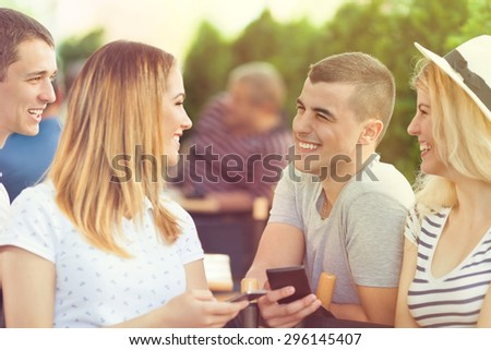 Young man flirting with a pretty young girl in a cafe - stock photo