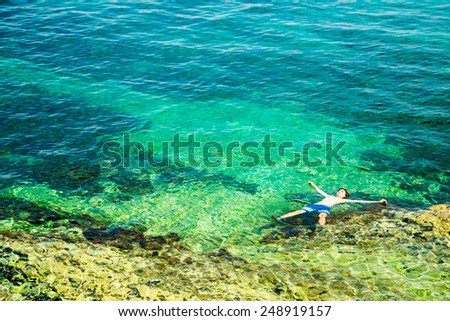 Young Man Floating in Crystal Clear Sea. Full Relaxation. Healthy Lifestyle Concept. Summer Vacation. Copy Space. - stock photo