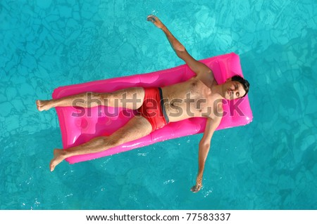 Young man floating on a mattress in water pool - stock photo