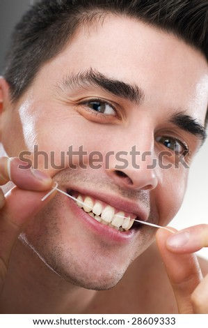young man flossing teeth close up shoot - stock photo