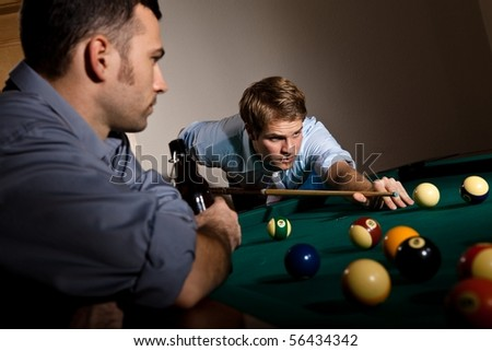 Young man focusing on playing snooker, concentrating on white ball friend watching at table. - stock photo