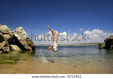 Young man full of energy jumping on the beach - stock photo
