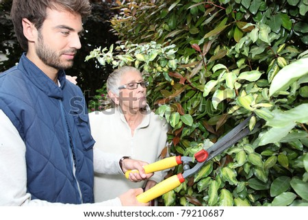 young man gardening with older woman - stock photo
