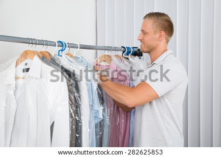 Young Man Getting Coat In Dry Cleaning Store - stock photo