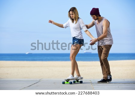 Young man gives his girlfriend her first skateboarding lesson on a seaside boulevard, during a lovely, calm summer afternoon. - stock photo