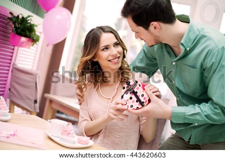 Young man gives present to his beautiful girlfriend  - stock photo