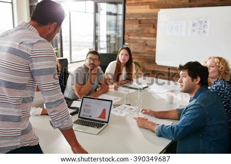 Young man giving business presentation on laptop to colleagues sitting around table in conference room. - stock photo