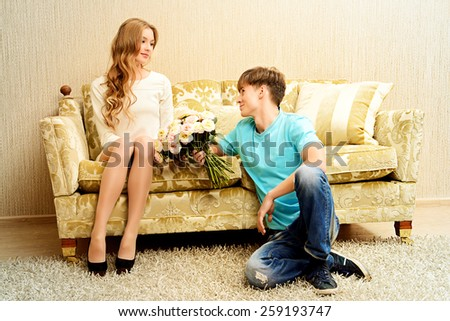 Young man giving flowers to his sweetheart. They are in the cozy living room. Family, love concept. - stock photo