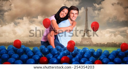 Young man giving girlfriend a piggyback ride against paris under cloudy sky - stock photo