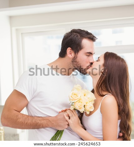 Young man giving girlfriend white roses at home in the kitchen - stock photo