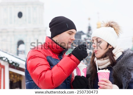 Young man giving his girlfriend a taste of his drink or takeaway dessert as they stand outdoors on a cold winter day in their knitted caps and scarves - stock photo