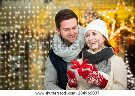 Young man giving his girlfriend Christmas present in front of holiday lighting - stock photo