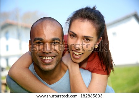 Young man giving piggyback ride to girlfriend - stock photo