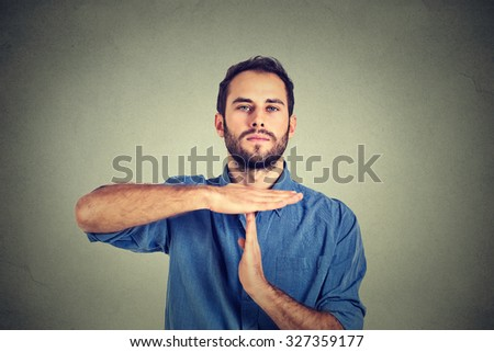 Young man giving showing time out hands gesture isolated on gray wall background  - stock photo