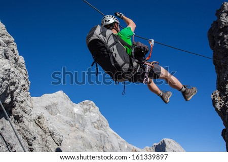 Young man going accross tyrolean traverse on via ferrata (Klettersteig) - stock photo