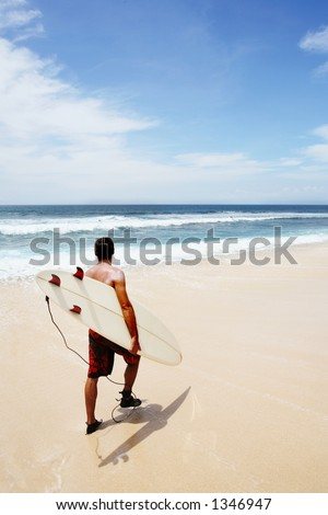 Young man going to surf at Dreamland, Bali - stock photo