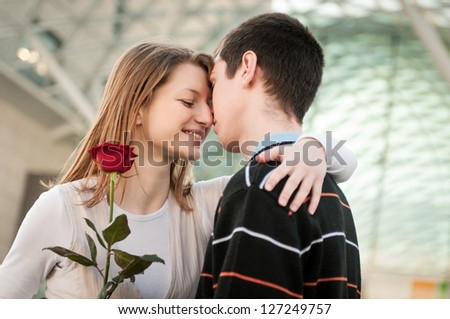 Young man handing over a flower (red rose) to woman - intimate moment - stock photo