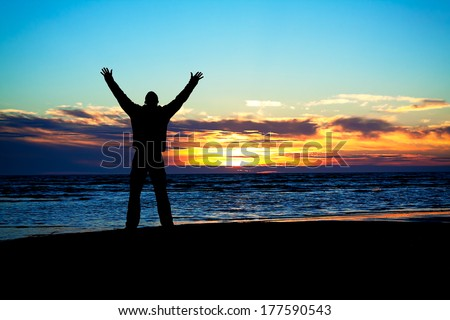 young man hands up on a beach at sunset - stock photo
