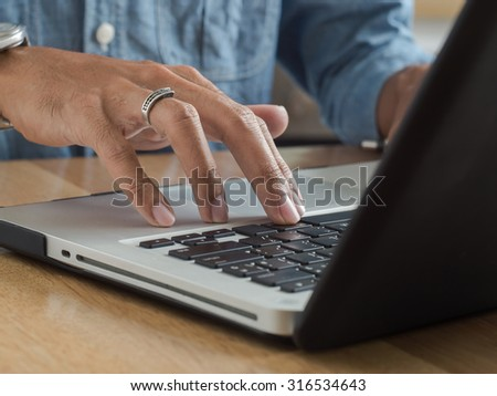 Young man hands using laptop computer keyboard on wooden desk. - stock photo
