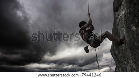 Young man hanging on a rope by a cliff - stock photo